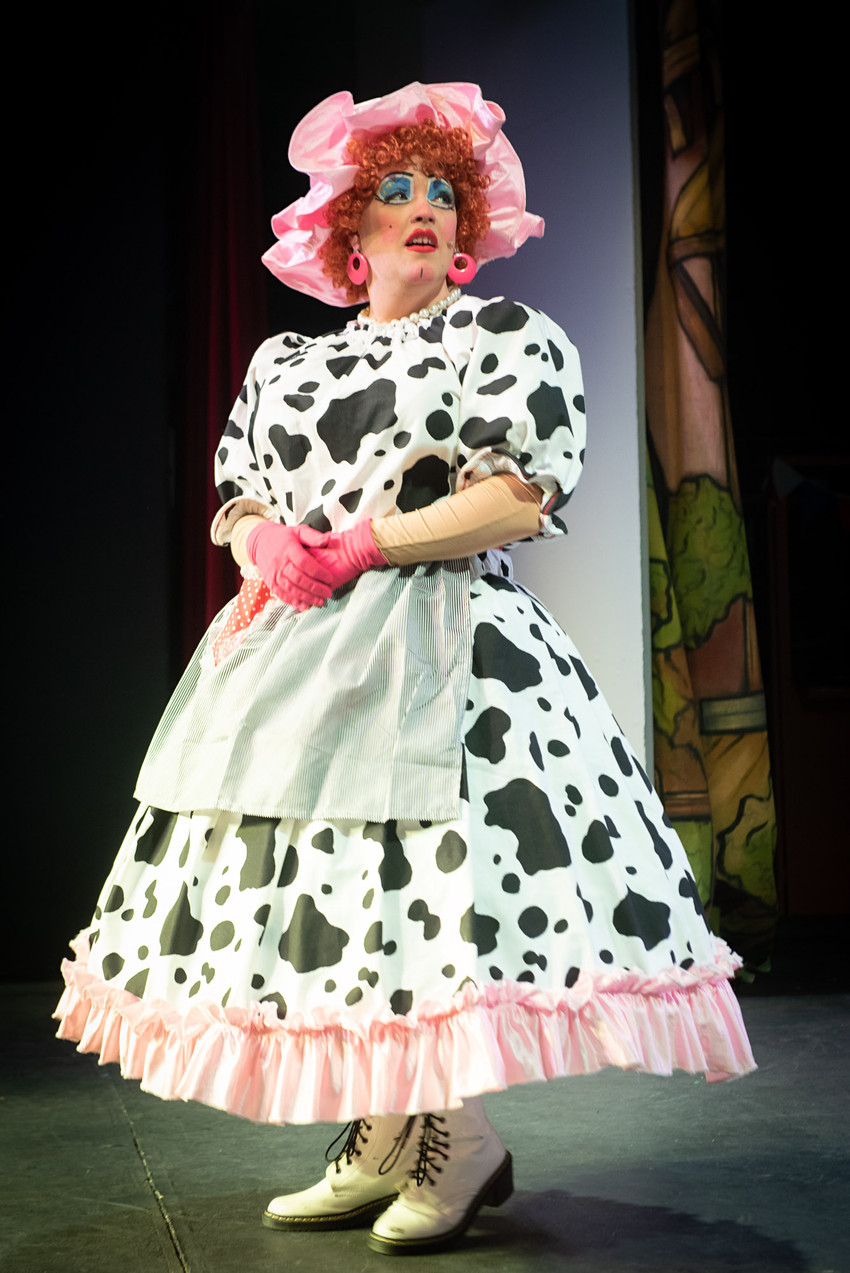 "Close up photograph from Bolton theatre production ""Jack and the Beanstalk"" of Dame Dotty Dimple looking surprised over her shoulder."