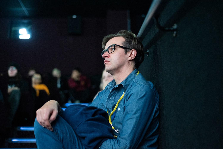Audience member sat on the steps in full auditorium