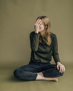 woman sitting down with one palm over her face indicating she is stressed.