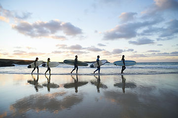 surfers walking in the ocean