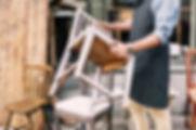 Mediana do homem segurando cadeira ao es