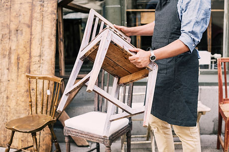 Midsection of man holding chair while standing against store