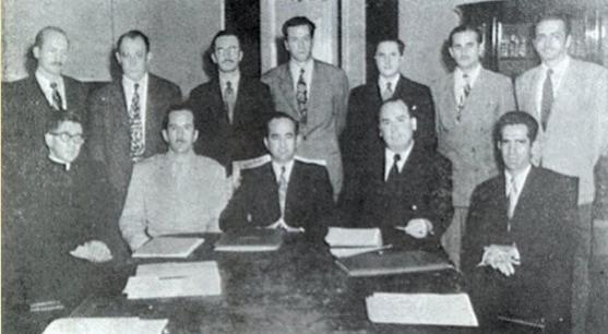 Foto antigua de la Junta Fundadora de la Segunda República, cinco hombres sentados y 7 de pie, ordenados en dos filas, frente a una mesa larga.