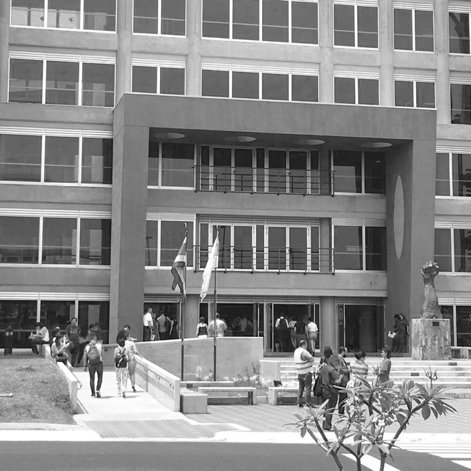 Plano general de la entrada la Facultad de Ciencias Sociales, donde varias personas entran y salen. A la izquierda se observa las banderas de Costa Rica y Universidad de Costa Rica. Al fondo a la derecha se observa la escultura de un puño.