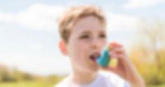 child using inhaler for asthma outside i