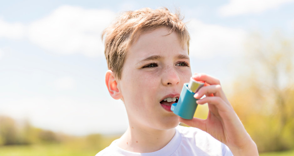 child using inhaler for asthma outside i
