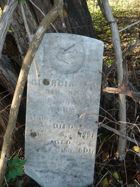 Georgia Braxton's tombstone, propped against a fencerow, symbolizes Ralls County's colorful