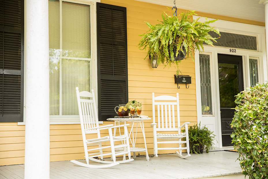 Two rocking chairs, pitcher of iced tea on a table in between on front porch.