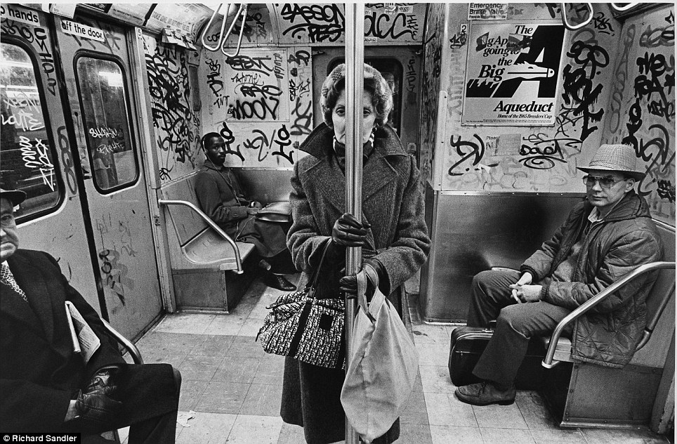 Training day- A woman stands in the graffiti-covered carriage of the C train in 1985 as other commut