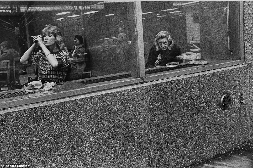 he stare- A woman applies make-up as she sits in the window of the Donnell Library in 1981 while ano