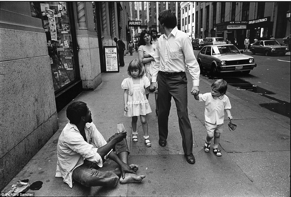 New York state of mind- Two children stare curiously at a homeless man as they walk with their paren