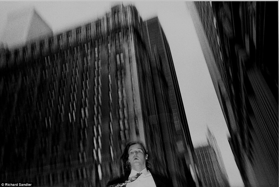 The streets of Manhattan- A suited man is captured on camera as he walks near Broadway and Wall Stre