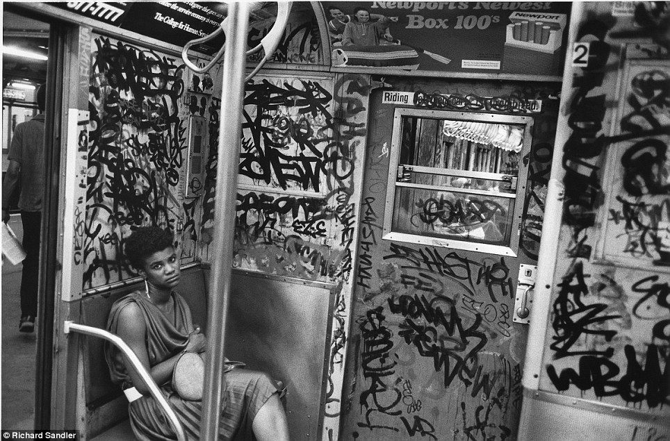 Tagged- A woman looks up from a subway car so covered in graffiti it's almost more paint than wall i
