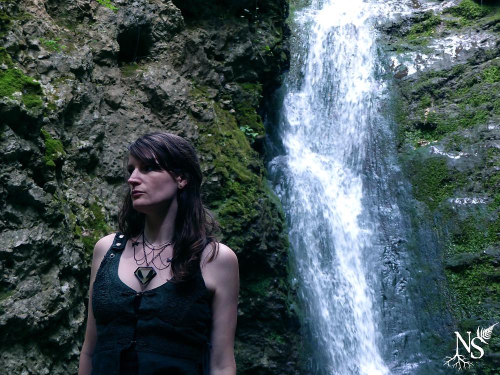 le collier aux libellules porté par une femme devant une cascade