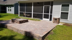 raised paver patio with gas fire pit in
