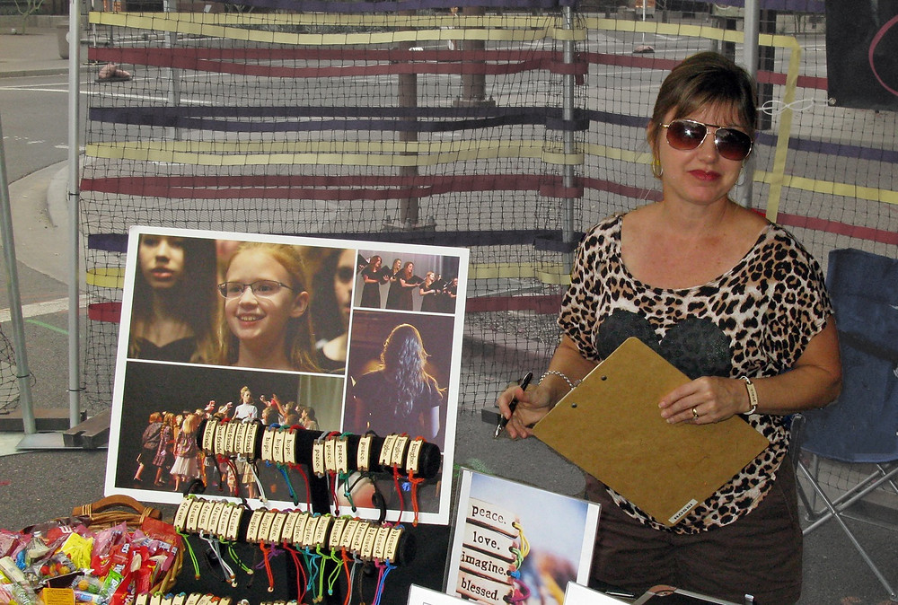 Woman with clipboard standing at a booth for recruitment and fundraising.