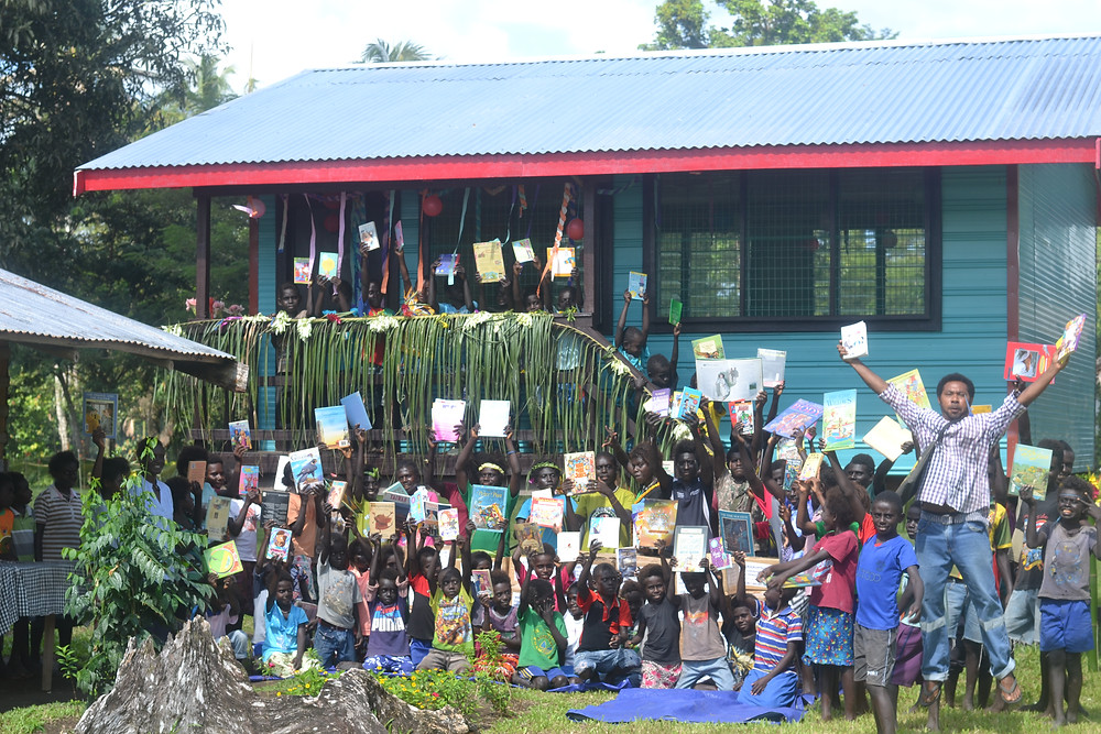 Students at Koruma Primary School celebrate with their books in front of a new library built by RRF