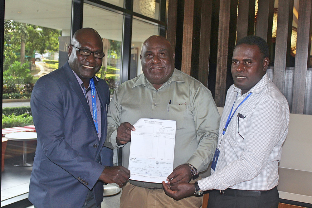 Hon Timothy Masiu (middle) handing over cheque to TKP Directors