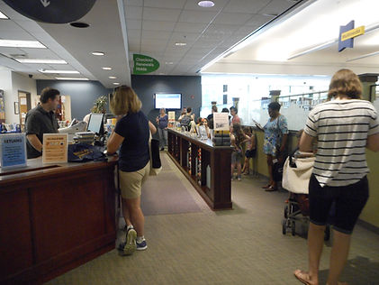 Picture of people waiting to check out items at our circulation desk.