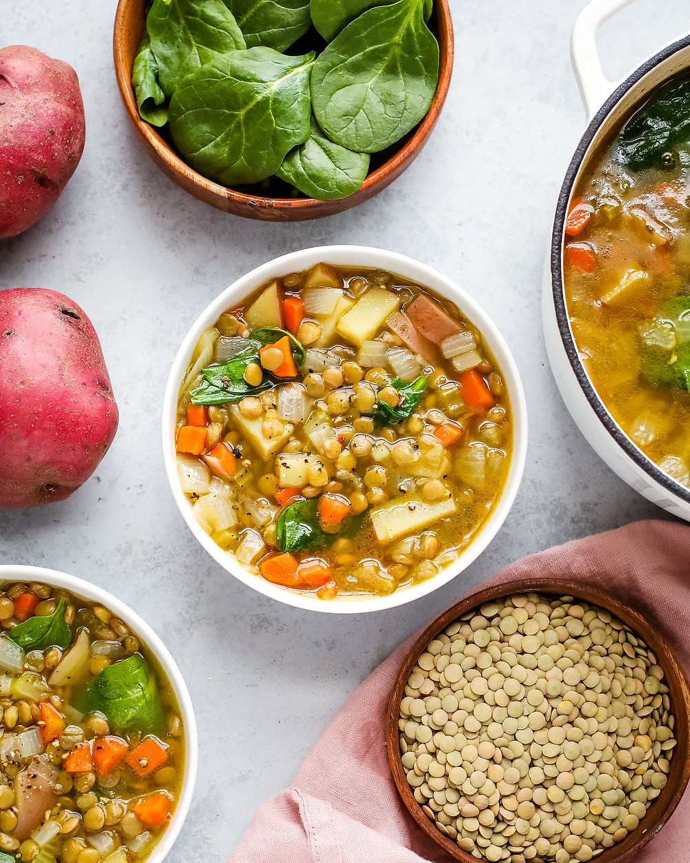 lentil soup in bowl surrounded by lentils and potatoes.