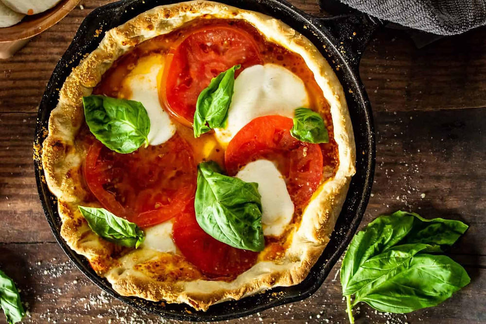 cast iron pan pizza with tomatoes, cheese, and basil.