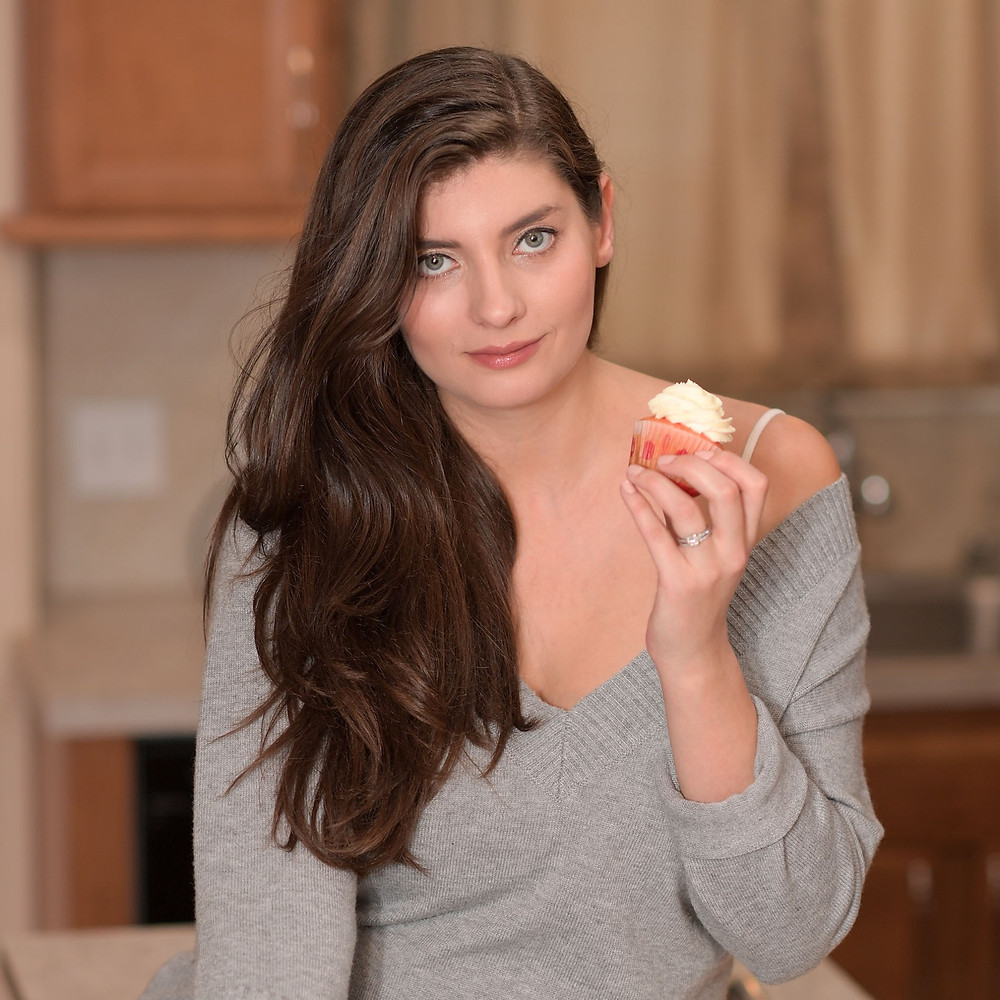 woman with long brown hair holding cupcake