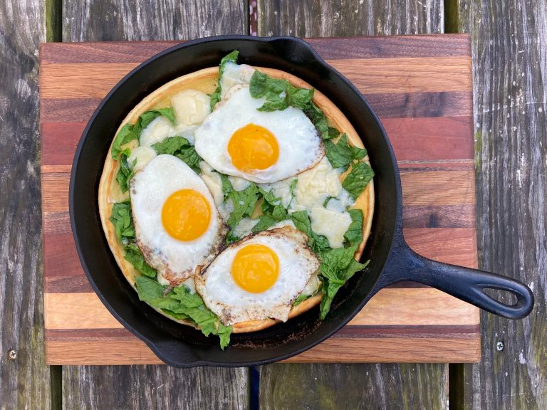 dutch baby pancake in cast iron skillet with fried eggs on top