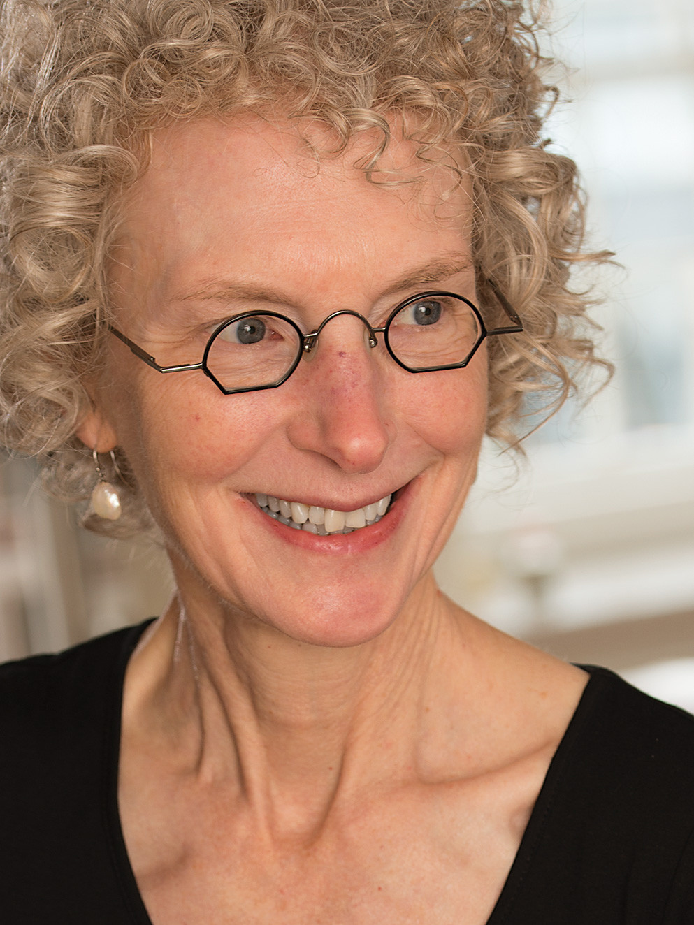 woman with curly blond hair wearing glasses and smiling