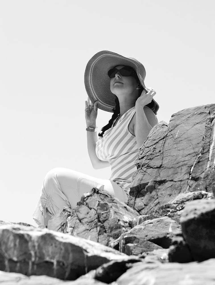 woman at the beach wearing sunglasses and large brimmed hat