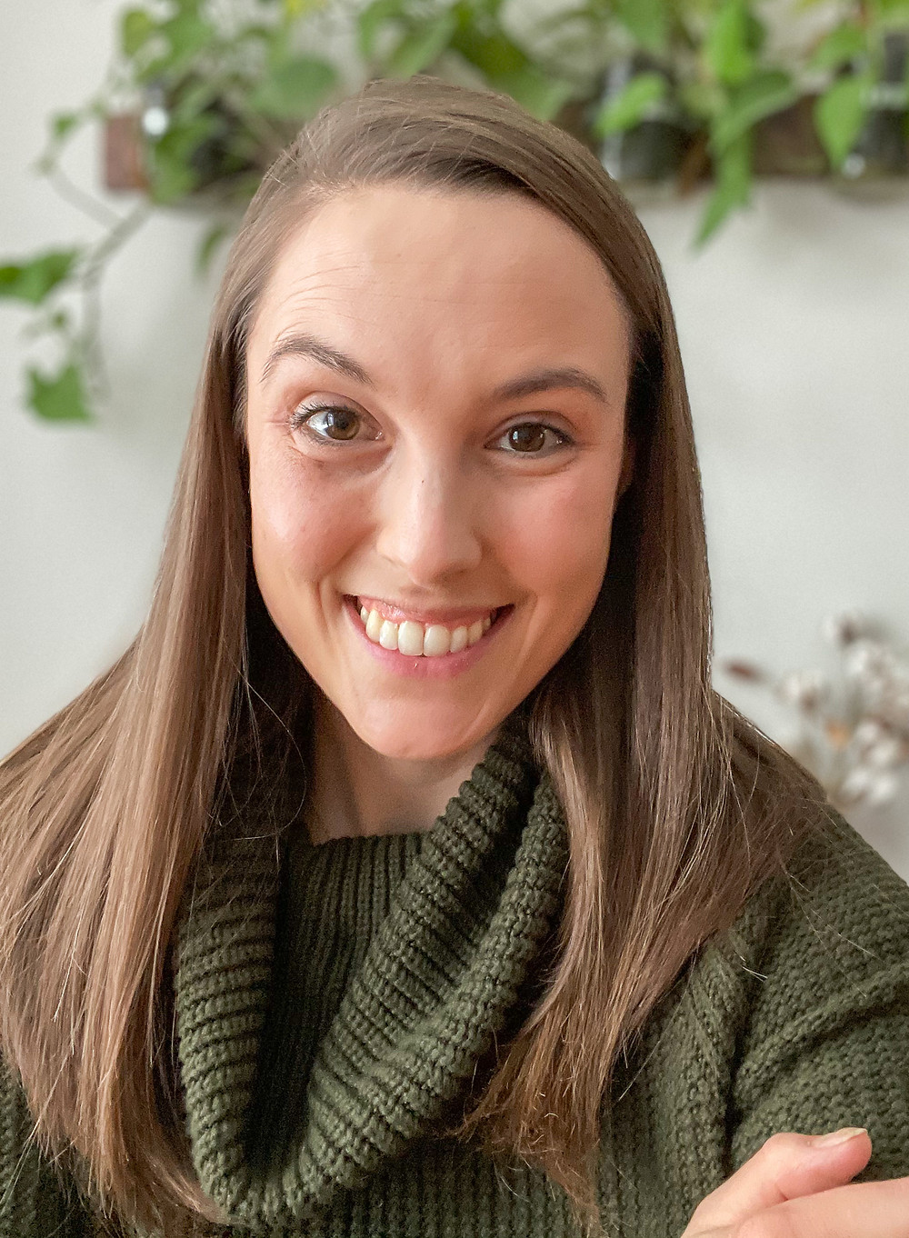 woman with brown hair and green sweater smiling