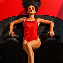 Model in red swimsuit posing on red spor