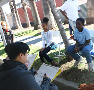 The ArtCenter Caricature Club sketches young attendees of the Pasadena Black History Parade Festival