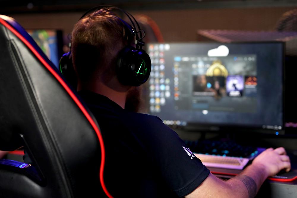 Man wearing headphones and working on a desktop computer