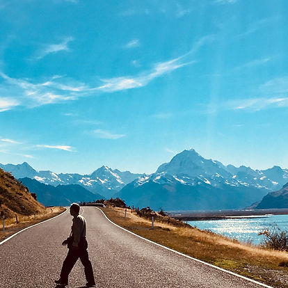 Man looking into the distance, with mountains in the background. Blue sky and lake.