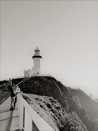 Two people looking over the cliff. With a lighthouse in the background. Grey and white background.