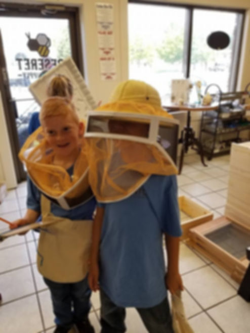 students try on beekeeper's suits at deseret hive