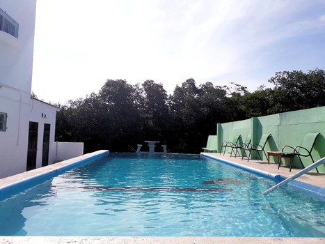 See Belize Infinity Pool with picnic table and deck chairs.jpg