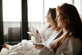 women-in-bathrobes-enjoying-tea-49GHBDY.jpg
