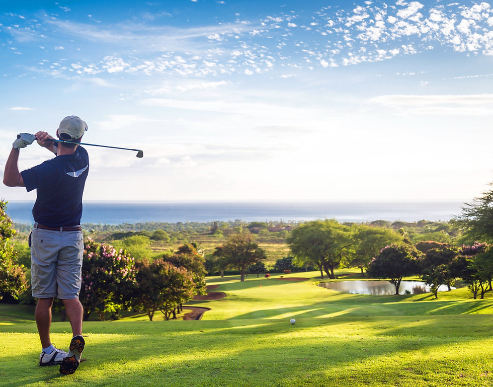 Man hitting golf ball down hill towards ocean and horizon_edited.jpg