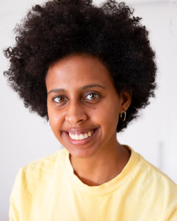 Photo of Michaela Gasteratou, a young Black women with caramel skin and big afro smiles at the camer