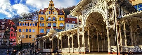 Tour de Karlovy Vary - UNITY Tours Praga. Karlovy Vary es una ciudad de cuento de hadas encajada en el río Tepla y todo el casco viejo de Karlovy Vary es un decorado historicista cuajado de edificios barrocos, art noveau y neoclásicos. Una unidad arquitectónica casi perfecta, rota solamente por dos o tres pastiches estalinistas de la época comunista. Karlovy se convirtió en el balneario más chic de Centroeuropa, frecuentado por la jet y la nobleza desde hace al menos 200 años. Es famosa históricamente por sus fuentes termales (13 fuentes principales y unos cientos más pequeñas) y el río Teplá, también de aguas calientes. Posee una interesante arquitectura.  Llegó a ser un famoso destino turístico en el siglo XIX, especialmente para personajes internacionales ilustres que buscaban tratamientos termales. La ciudad es conocida por el Festival Internacional de Cine de Karlovy Vary y el popular licor checo Karlovarská Becherovka.