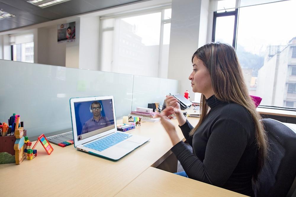 Imagen de una mujer ubicada en una oficina, frente a un computador, comunicándose por lenguaje de señas.