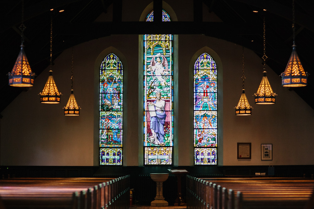 Ornate stained glass church windows in front of wooden pews