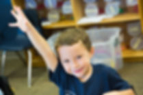 Boy with raised hand, smiling.jpg