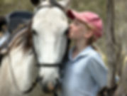young girl rider kissing a white horse.j