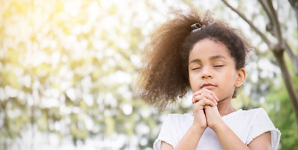 Portrait of little cute girl praying in