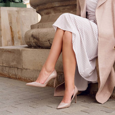 Closeup fashionable woman legs wear beige high heel shoes, dress and sitting. Outdoor fall