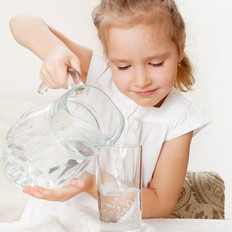 Child with glass pitcher water. Little g