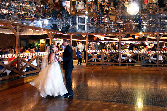 Newlywed couple on the dance floor surrounded by guests seated at tables
