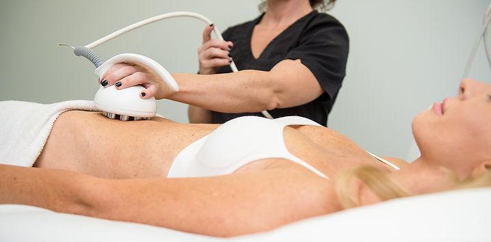 Une technicienne qui fait un traitement Venus Freeze, remodelage corporel, sur le ventre d'une cliente féminine